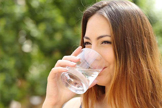 photo of woman drinking glass of water