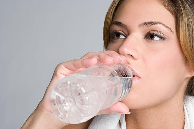photo of woman drinking bottled water